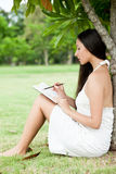 Girl at the park writes in her personal diary Royalty Free Stock Image