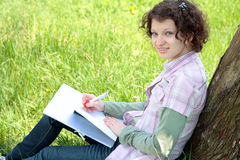 Girl  in park writes in writing book Royalty Free Stock Image