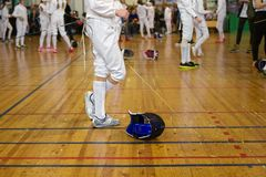 Girl participant in the fencing competition on swords is in the center of gym. Holding a sword in her hand, waiting for next battle. Fencing mask is on the Stock Images