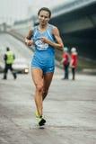 Girl participant of marathon runs through streets of city Royalty Free Stock Image