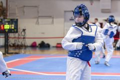 A girl participating in Taekwondo competitions in a blue protective vest and a protective helmet is a duel in Taekwondo against th royalty free stock images