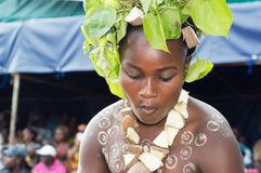 Girl at a party in africa. Bassam ,  Côte d`Ivoire  – November  7 ,  2015 :  young woman painted on the body by caollin, slices of yam as a cheese and leaves Royalty Free Stock Photo