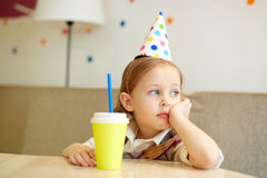 Girl at party. Lonely girl in birthday cap holding plastic glass with soda Stock Photos