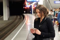 The girl passenger with a ticket in hand waiting for subway train. People in the background Stock Photos