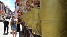 Girl passes by prayer wheels stock footage
