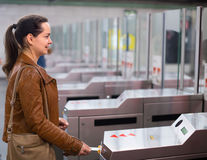 Girl passing ticket barrier in subway Stock Images