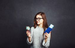 Girl with Passport and Plane Ticket. Cheerful girl holding passport, plane ticket and globe before grey background, indoor travel concept Royalty Free Stock Photo