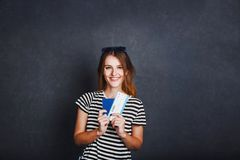 Girl with Passport and Plane Ticket. Cheerful girl holding passport, plane ticket and globe before grey background, indoor travel concept Royalty Free Stock Photography