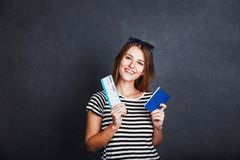 Girl with Passport and Plane Ticket. Cheerful girl holding passport, plane ticket and globe before grey background, indoor travel concept Royalty Free Stock Images