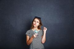 Girl with Passport and Plane Ticket. Cheerful girl holding passport, plane ticket and globe before grey background, indoor travel concept Stock Photos