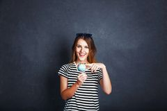Girl with Passport and Plane Ticket. Cheerful girl holding passport, plane ticket and globe before grey background, indoor travel concept Stock Images