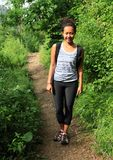 Girl on path in Slovak Paradise. Young Papuan woman - smiling traveling girl on path among bushes in Slovak national park Slovak Paradise in Slovak Republic royalty free stock photo