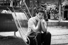 Girl pauper sitting alone at playground Stock Photo