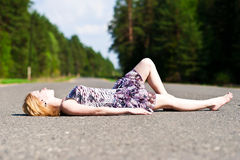 The girl on the pavement. Young girl lying in the middle of the road Stock Image