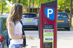 Girl paying for parking, Milton Keynes Royalty Free Stock Images
