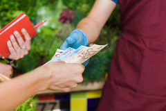 Girl pays for cash on the market Royalty Free Stock Photo