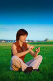 Girl with PDA. Girl works in the meadow with PDA Stock Photography