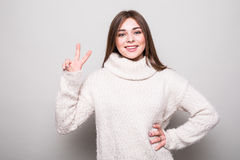 Girl with peace sign in sweater in studio Stock Images