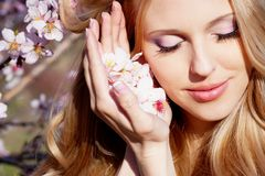 Girl with peach flowers near face Stock Photography