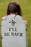 Girl peaking over headstone Stock Photo