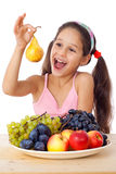 Girl with pear and plate of fruit Stock Photography