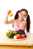 Girl with pear and plate of fruit Royalty Free Stock Photography