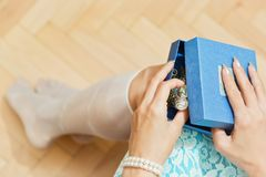 Girl with pearl bracelet unboxing Christmas gift. Young female person dressed  in blue unpacking a gift box with a Christmas, New Year or Valentine present Royalty Free Stock Photo