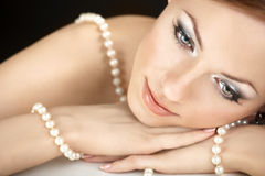 The girl with pearls. The dreaming woman with a pearl necklace on the bared shoulders Royalty Free Stock Photos
