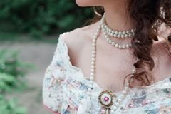 A girl with pearls and bare shoulders stock photo