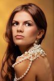 Girl with pearls necklace. Portrait of young woman with pearls necklace on golden background royalty free stock photo