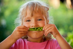 Girl with peas Stock Photos
