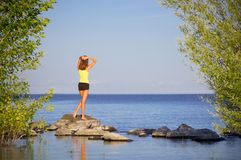 Girl on pebbles at sea shore Stock Photography
