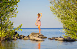 Girl on pebbles at sea shore Royalty Free Stock Images