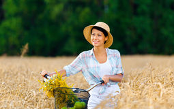 Girl pedals bicycle with apples and flowers in rye field Royalty Free Stock Images