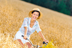 Girl pedals bicycle with flowers in rye field Royalty Free Stock Photography