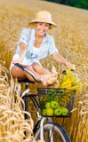 Girl pedals bicycle putting legs on it in rye field Royalty Free Stock Images