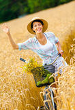 Girl pedals bicycle and waves hand in rye field Royalty Free Stock Photos