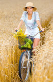 Girl pedals cycle with apples and flowers Royalty Free Stock Images