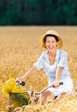 Girl pedals cycle with flowers in rye field Royalty Free Stock Photo