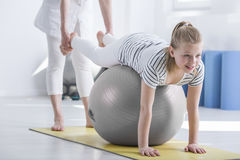 Girl during pediatric occupational therapy. Smiling young girl lying on ball during pediatric occupational therapy stock image