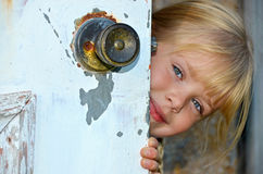 Girl peeking around door Royalty Free Stock Image