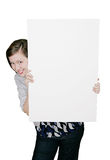 Girl peeking around sign. A beautiful young woman peeking around a blank sign Royalty Free Stock Images