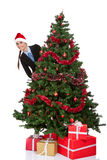 Girl peeking  behind christmas tree Royalty Free Stock Photos