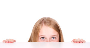 Girl peeking from behind table Royalty Free Stock Photo