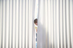Girl Peeking From Curtains At Home. Portrait of little girl peeking from curtains at home Royalty Free Stock Image