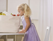 Girl Peeking in Grocery Bag Stock Photos