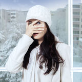 Girl peeking through her fingers. Young girl wearing winter clothes and peeking at the camera through her fingers near the window Stock Photo