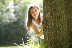 Girl (7-9) peeking out from behind tree, smilng, portrait Stock Photo