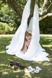 Girl Peeking Out Of Sheet Tent In Backyard. Young girl peeking out of tent made of sheet in the backyard Stock Photos