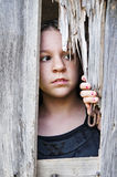Girl peeking out of wooden door Royalty Free Stock Images